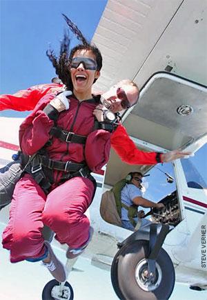 Tandem skydiving pair exits a Cessna 182.